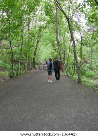 A couple strolls down a tree lined path. - stock photo