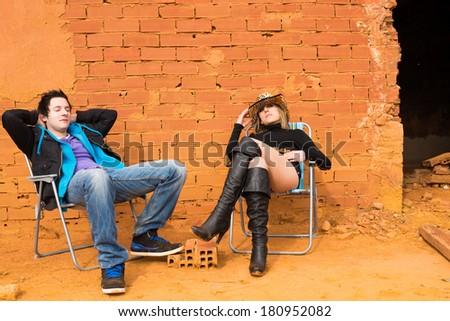 A couple sunbathing among derelict ruins, a concept - stock photo