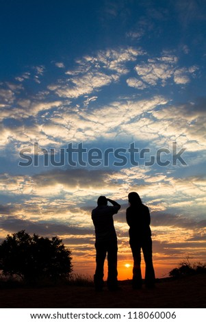 A couple taking photographs of a spectacular sunset in the Kalahari desert