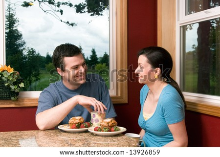 A couple talking over breakfast by a large window, with picturesque background, at home.  Horizontally framed shot. - stock photo
