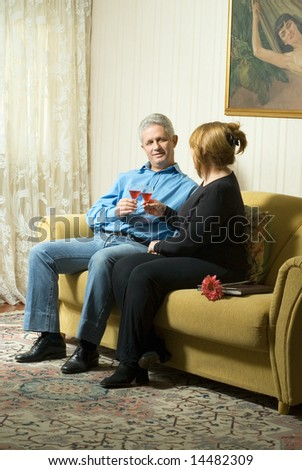 A couple toasting wine glasses.  They are seated on a couch and the man is smiling. Vertically framed shot. - stock photo
