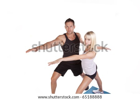 a couple training and doing yoga stretches together with serious expressions on their faces. - stock photo