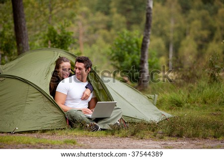 A couple using a computer outside a tent on a camping trip