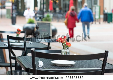 A couple walk hand in hand along an outdoor mall. In the foreground is a black metal table with a simple arrangement of roses with a white napkin and plates.  - stock photo
