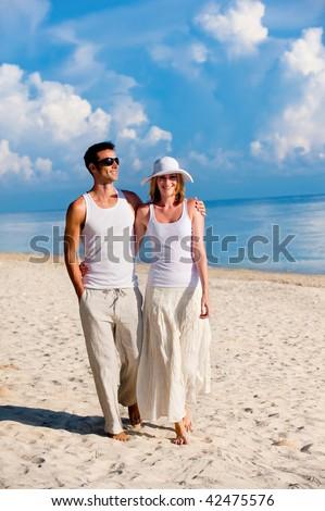 A couple walking along a sandy beach - stock photo