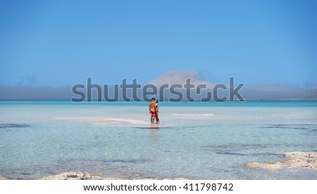 A couple walking and hugging in the sea - stock photo