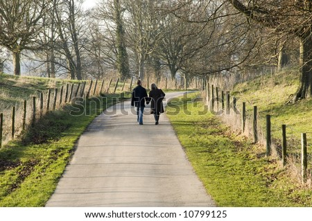 A couple walking in the countryside. - stock photo