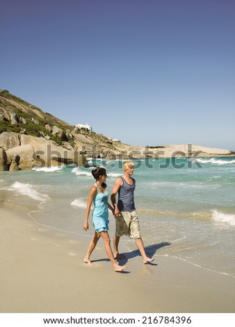 A couple walking on the beach. - stock photo