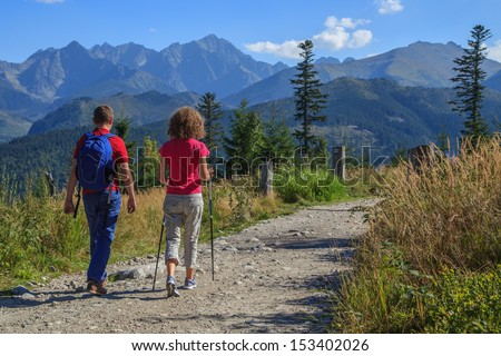 A couple walks a path to the mountains in Tatra National Park, Poland - stock photo