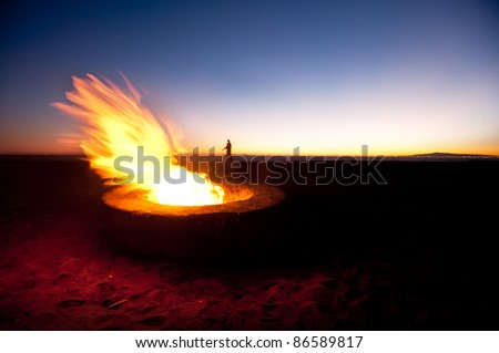 A couple walks along a beach behind a large fire during sunset.