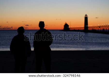 A couple watching the sunset at the Grand Haven South Pierhead Lighthouse in Grand Haven State Park in Grand Haven, Michigan - stock photo