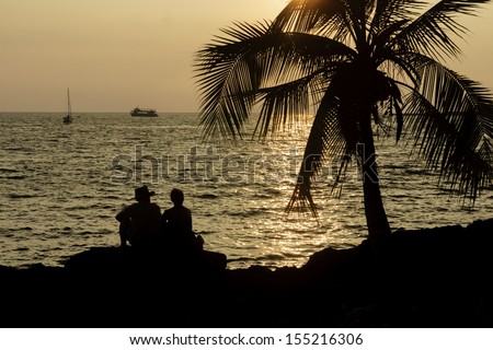 A couple watching the sunset in Kailua Kona, Hawaii, USA - stock photo