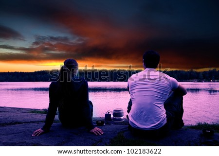 A couple watching the sunset while camping by a lake - stock photo
