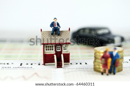 A couple with suitcases walking away from their house & mortgage after a bank has repossessed their house, with the bank manager sitting pretty on top of their house with his flash car parked nearby. - stock photo