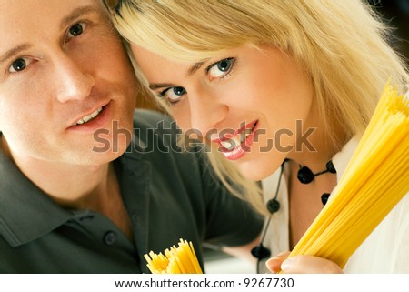 A couple with uncooked spaghetti (going to prepare them presumably) - stock photo