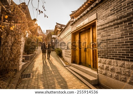 A couple women wander through the traditional style houses of Bukchon Hanok Village in Seoul, South Korea. - stock photo
