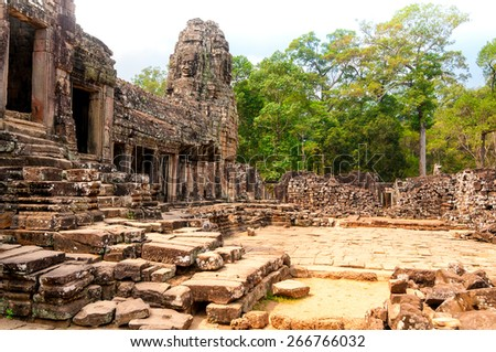 A courtyard of the Bayon temple at Angkor Wat, Cambodia, with the main edifice at left - stock photo