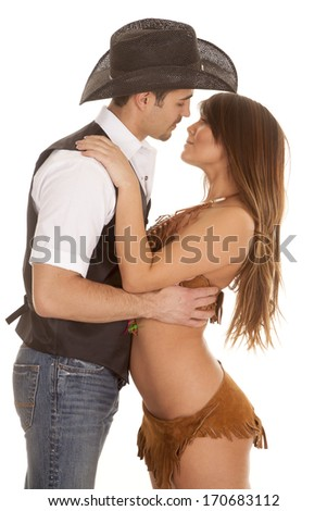 A cowboy and Indian couple are embracing and are about to kiss. - stock photo