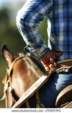 A cowboy awaits the action while sitting on his horse.