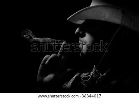 a cowboy blow  off smoke from his hand-gun - stock photo