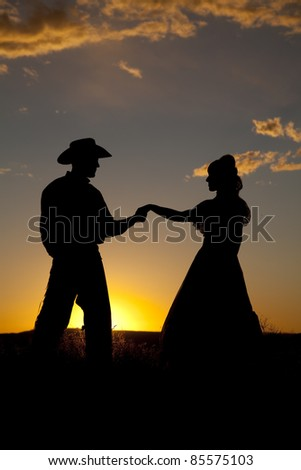 A cowboy couple is silhouetted in the sunset and holding hands. - stock photo