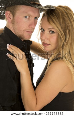 A cowboy cuddling with his woman looking at the camera. - stock photo