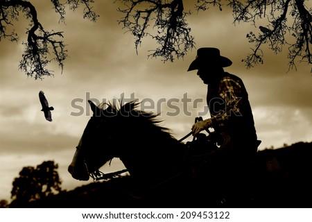 A cowboy gallops down a hill to escape danger.  Sepia tone, black branches, and birds. - stock photo