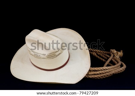 a cowboy hat and lasso on a black background - stock photo