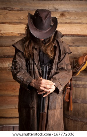 A cowboy holding on to he weapon with his head down. - stock photo
