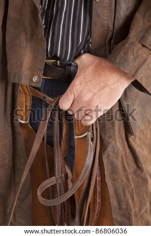 A cowboy holding on to his belt while he holds on to his bridle.