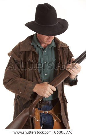 A cowboy holding on to his rifle holding his gun in his hands. - stock photo