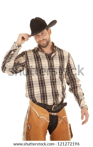 A cowboy holding on to the brim of his hat with a smile on his face. - stock photo