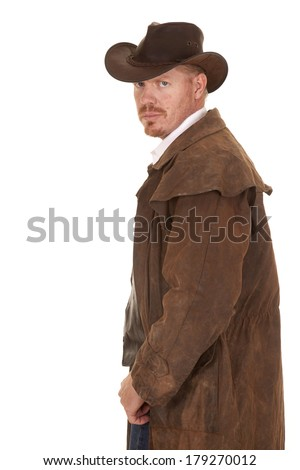A cowboy in a leather coat looking back over his shoulder. - stock photo
