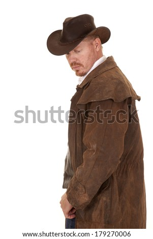A cowboy in a leather duster looking down. - stock photo