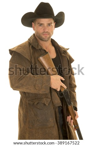 A cowboy in his western duster holding on to his rifle ready to shoot.