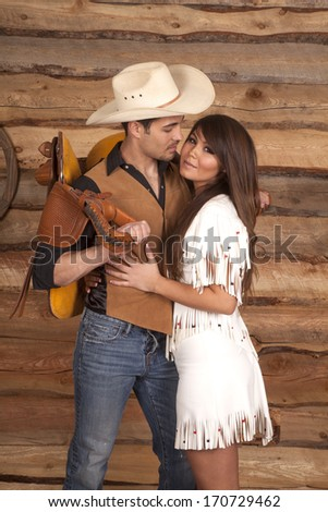 A cowboy is holding a saddle on his back while looking at an Indian. - stock photo