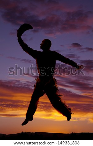 A cowboy is holding his hat and jumping in the sunset. - stock photo