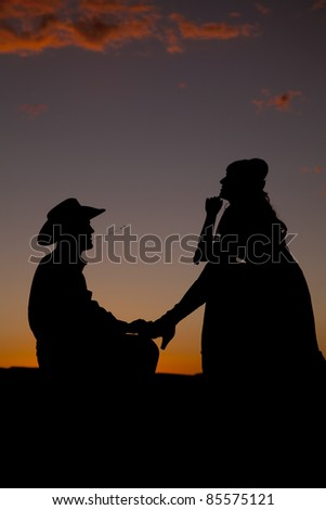 A cowboy is on his knees in the sunset with a woman by with one leg on him.