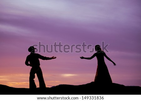 A cowboy is reaching back for a woman in the sunset. - stock photo