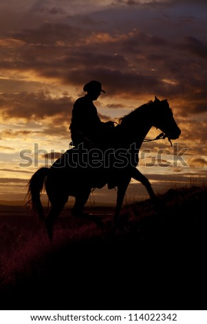 A cowboy is riding his horse up a hill in the sunset. - stock photo