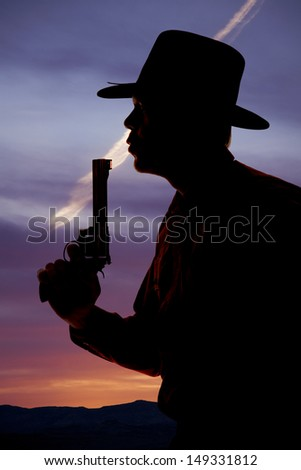 A cowboy is silhouetted with a pistol blowing on the end. - stock photo