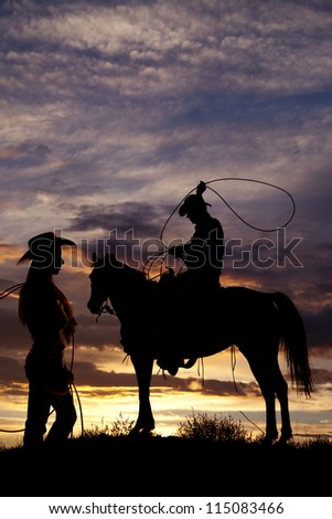 A cowboy is sitting on a horse in the sunset swinging a rope with the silhouette of a cowgirl standing off to his side holding on to her rope.