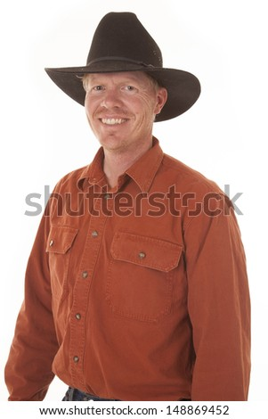 A cowboy is standing and smiling with a black hat on.