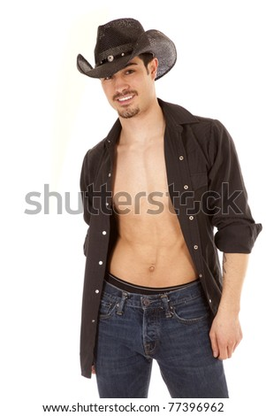 A cowboy is standing and smiling with his shirt unbuttoned. - stock photo