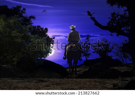 A cowboy riding his horse into the night in a deep blue setting. - stock photo