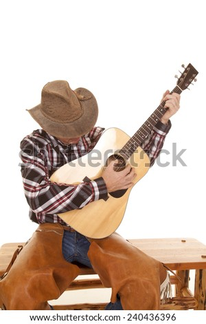 a cowboy sitting and playing his guitar looking down. - stock photo