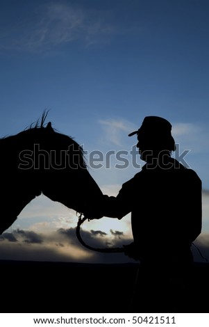 A cowboy touching the head of his horse in the sunset.