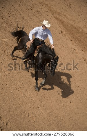 A cowboy training and riding his horse in the dusty dirt.