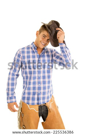 A cowboy with a smile putting his hat on his head, in his chaps. - stock photo