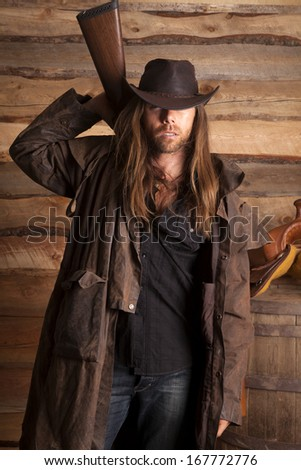 A cowboy with his duster on and a rifle behind his back. - stock photo